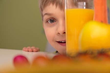 オレンジ ジュースのガラスの後ろに隠れている少年 写真素材
