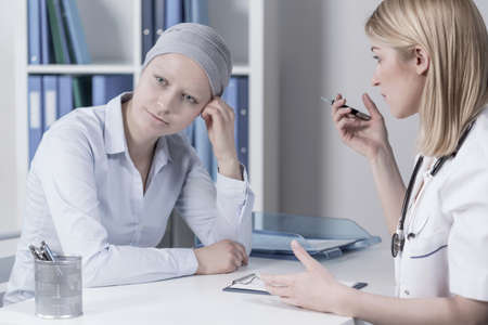 Young businesswoman with cancer in doctors office