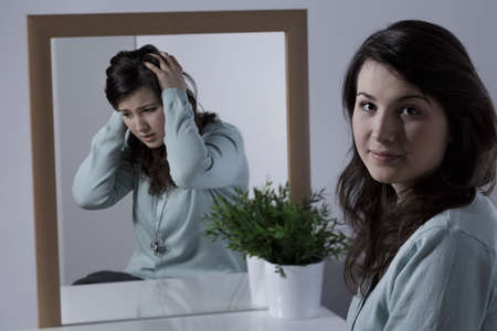 mental disorder: Young woman with depression hiding her emotions