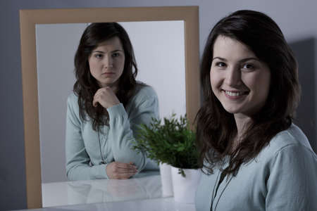 espejo: Mujer joven sola con trastorno de la personalidad bipolar