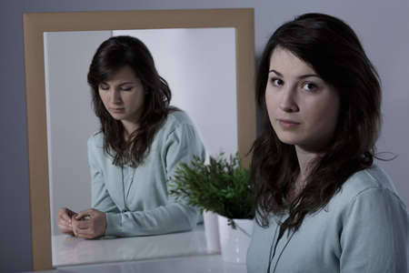 hypocritical: Depressed lonely woman repressing her real emotions Stock Photo