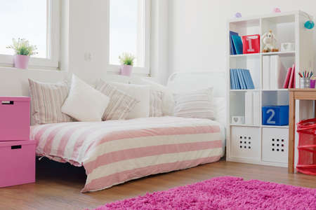 女の子の部屋でベッドの上のクッションの多く