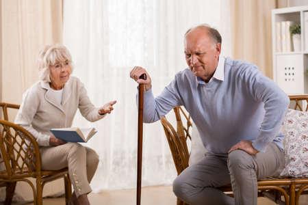 Senior man met knie artritis en zorgzame vrouw Stockfoto