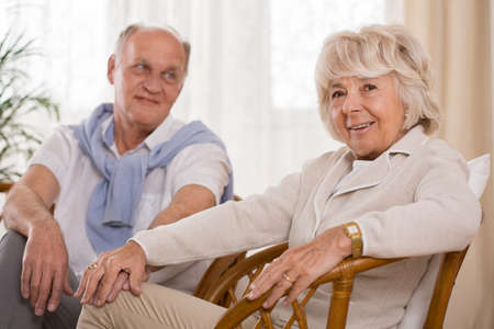 Caring senior woman holding hand her husband
