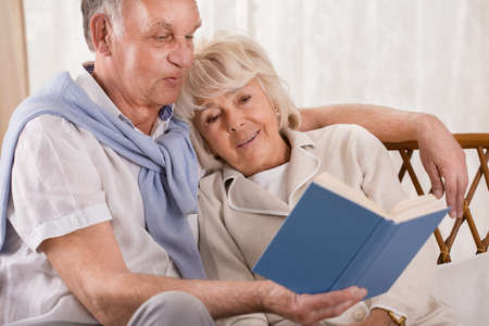 reading: Loving senior couple reading together interesting book
