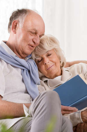 Senior man reading book and embracing sleeping wife Stock Photo