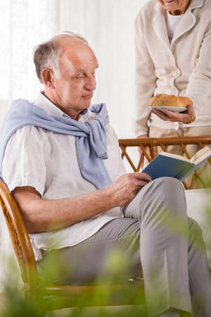 Retiree reading book and his caring wife Stock Photo