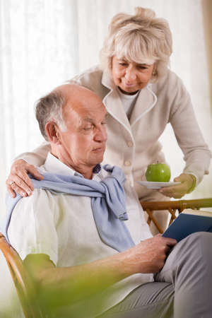 Senior woman caring about husband and serving an apple Stock Photo