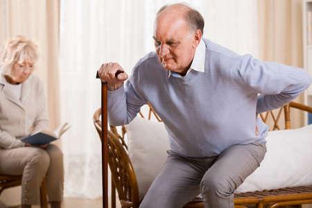 Gepensioneerde man met wandelstok met rugpijn Stockfoto