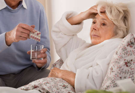 staying: Ill woman staying in bed and caring husband