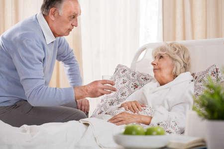 Loving husband caring about ill senior wife Stock Photo