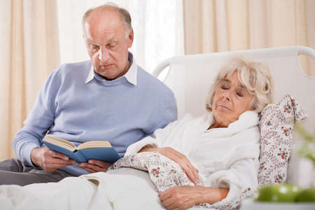 Image of husband reading ill wife book Stock Photo