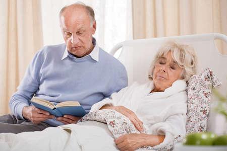 mujeres mayores: Imagen de marido leyendo el libro esposa enferma Foto de archivo