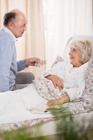 man in hospital bed: Ill senior woman in bed and assisting husband