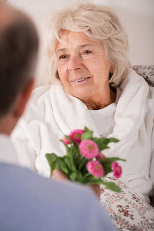 Senior man giving ill wife daisy bouquet
