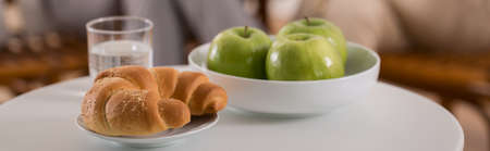 Croissant and green apples on the table