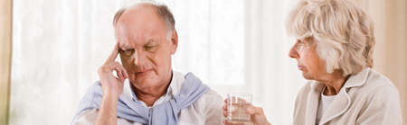 Senior man with migraine and assisting wife