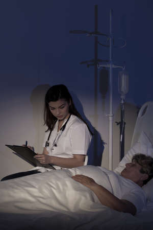 seriously: Doctor caring about terminally ill patient at night Stock Photo
