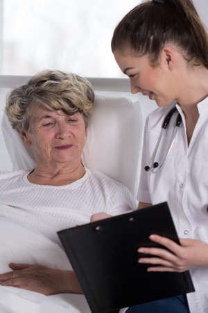 geriatrician: Geriatric patient lying in bed and young nurse Stock Photo