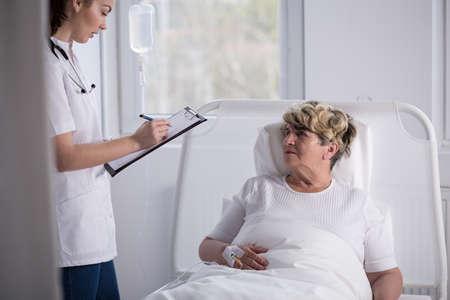 geriatrician: Geriatrician talking with senior woman in hospital Stock Photo
