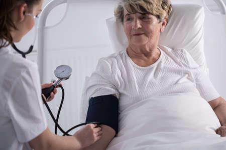 Nurse measuring blood pressure in hospital ward Stock Photo