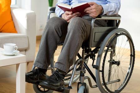 persona en silla de ruedas: Hombre en silla de ruedas que lee un libro, horizontal Foto de archivo