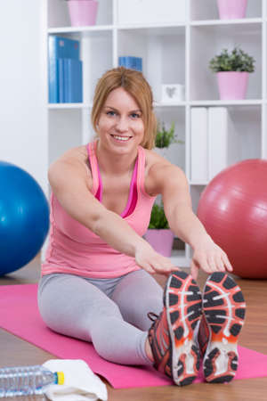 Cheerful fit girl stretching after home workout
