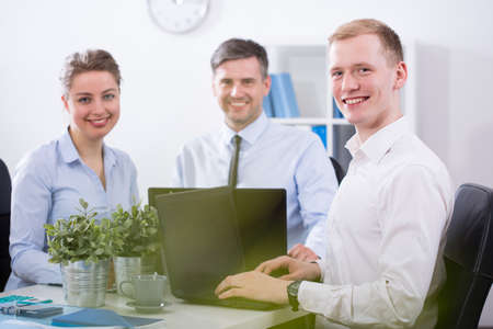 Smiling business team working together in corporation Stock Photo