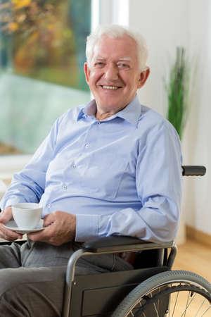 Happy elder man on wheelchair drinking coffee