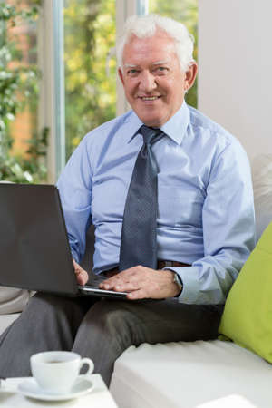 Vertical view of old man with laptop