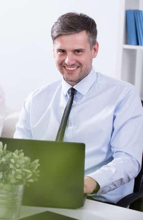Smiling mature businessman sitting at the desk