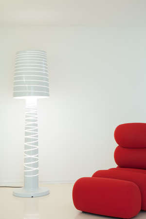 Modern red armchair and white extravagant lamp
