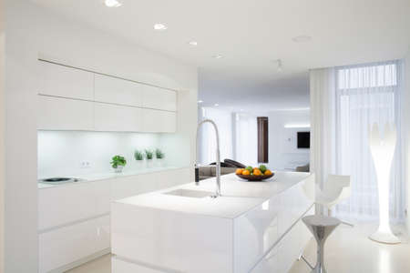 White clean kitchen with island in the middle