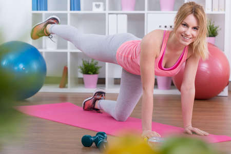 Happy fit woman exercising bottom muscles on mat