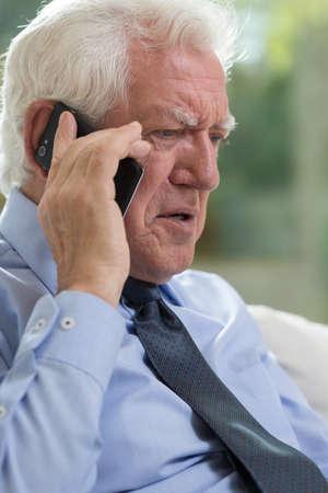 Elderly man talking on mobile phone, vertical