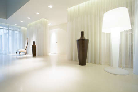 Spacious empty room with white lighted lamp