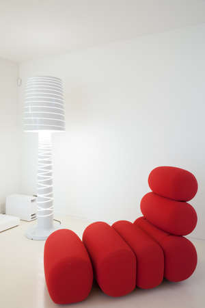 red sofa: Picture of unusual armchair and fancy white lamp