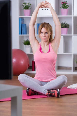 Pretty girl stretching arms in front of television