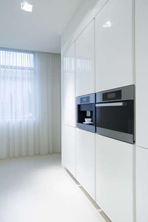 White kitchen units with new built-in oven Stock Photo