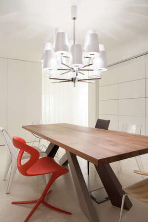 Wooden table in elegant dining space in modern home