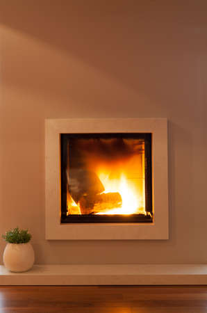 lighted: Warm lighted fireplace in modern lounge Stock Photo
