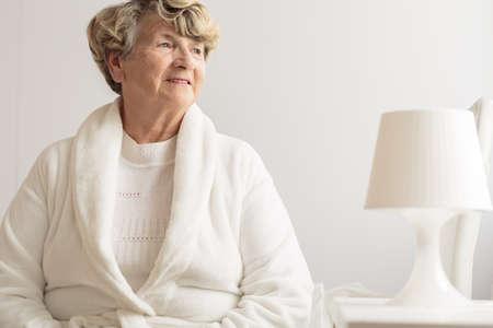 ガウンを着て家で年配の女性 写真素材