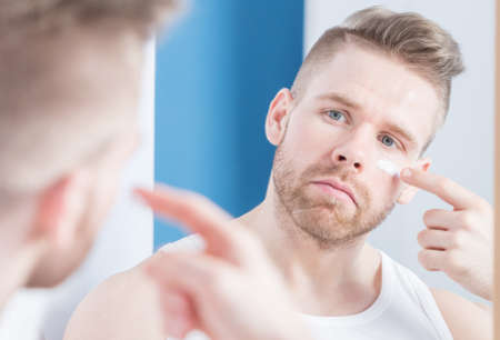 narcissistic: Guy applying facial cream in the bathroom