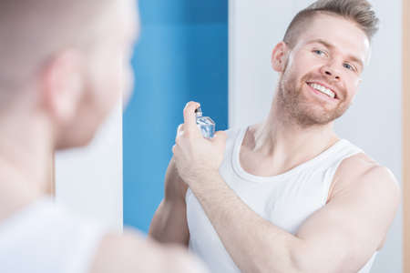 Reflection of smiling handsome guy applying perfume Stock Photo