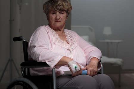 female catheter: Sad ill retiree sitting on a wheelchair