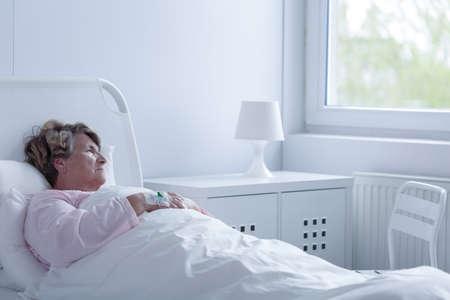 Zieke senior vrouw die in het ziekenhuis bed Stockfoto