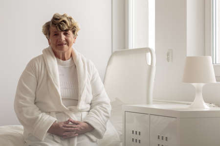 病院の部屋でバスローブを着て年配の女性