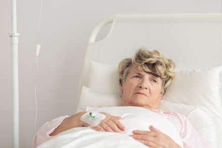 intravenous: Aged woman with intravenous cannula lying in bed