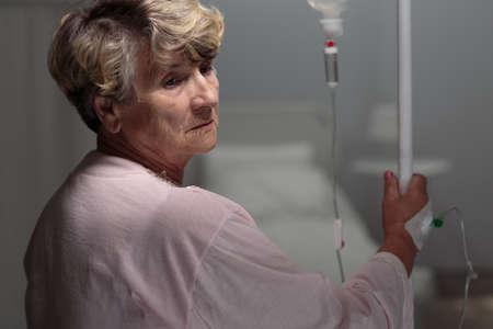 female catheter: Female retiree walking with an IV drip