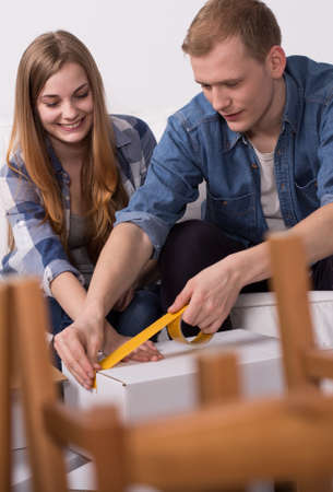moving box: Close-up of couple sealing a moving box